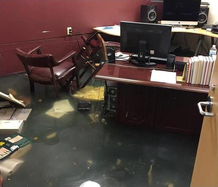 office flooded, desk, computer, files, documents floating on floodwaters