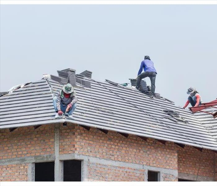 Workers working on roof tiles